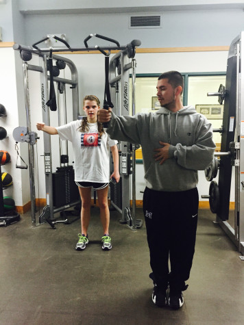 Ron Morales coaches a student during Thursday weight room training session.
