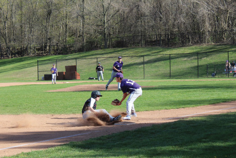 A Trevor Day player kicks up some dirt as he slides safely into 3rd base during a game at Clarke Field.  The Panthers, however, prevailed by a score of 7-4 in their first game of the season after many delays, mostly due to rainouts.