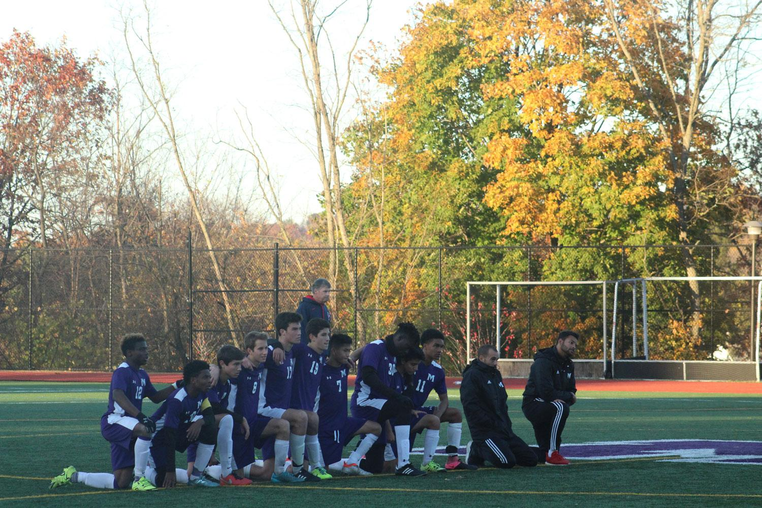 The Boys Varsity Soccer team kneels as they watch their teammates shoot penalty kicks.