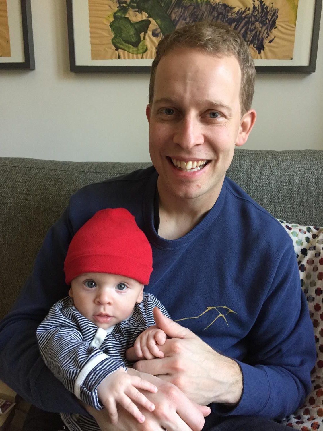 Darren Wood sits at home with his newborn son, Owen.
