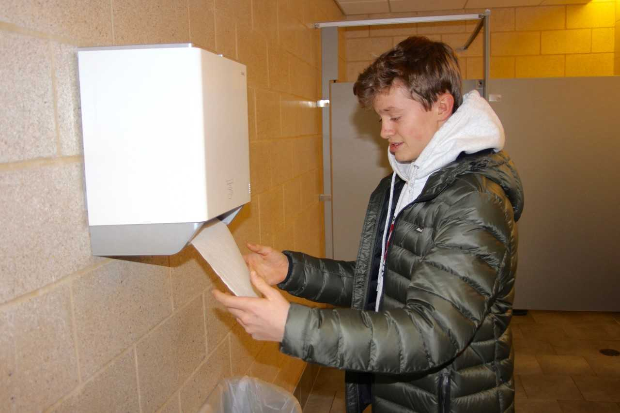 Sophomore Aidan Lothian grabs a paper towel from the automatic dispenser in the bathroom on the third floor of the FC. While the dispensers have a variety of benefits, they still produce a significant amount of waste.