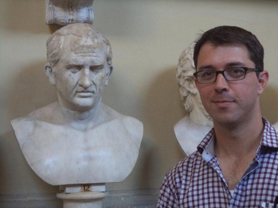 Latin teacher Keith Kitchen poses next to a statue of Cicero.
