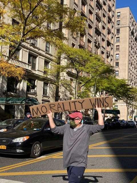 A man celebrates the media's projection of Biden as the winner of the presidential election. He was one of many waving signs on the streets of the Upper West Side. Some students, like Iris Pelli-Walbert, took to the streets to express their happiness with the results of the election.