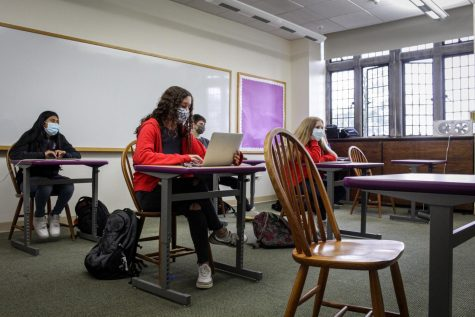 Students sit in rows as they participate in a hybrid class.  The desks which now occupy classrooms were a replacement for Harkness tables, which helped to facilitate the school