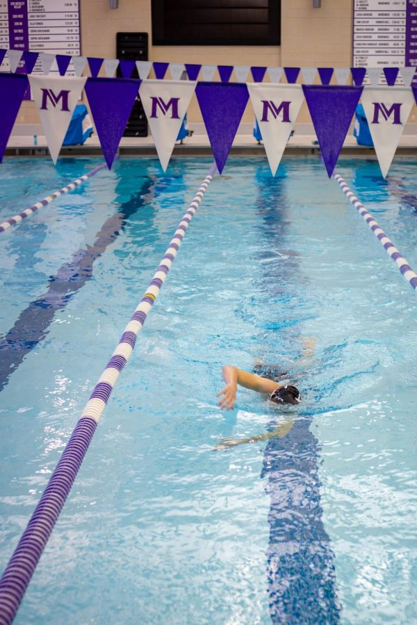 A Masters student swims alone in one lane during an afternoon practice.