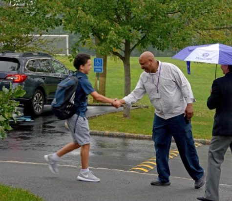 The late Masters security guard Panton Adams greets students outside the Middle School in the pouring rain on the first day of school in 2017. Adams, notorious for knowing every student