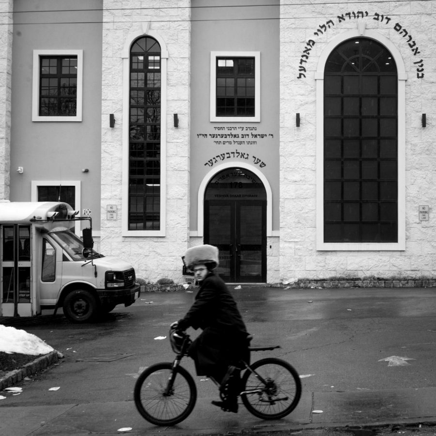 A Jewish Orthodox man drives a bicycle through Monsey, a town in Rockland County, N.Y.