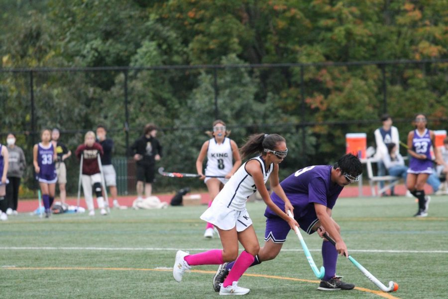 Sophomore Shaoquan Jerome Chen shields the ball from an opponent in the varsity field hockey game against King on October 13. The Panthers lost the game 4-0 in their first competition in over three weeks. This marked the teams fourth game ever being co-ed.